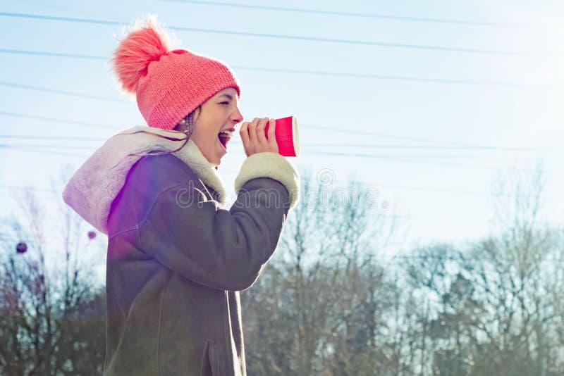 De winter openluchtportret van het jonge meisje gillen in een megafoondocument kop, exemplaarruimte royalty-vrije stock afbeelding