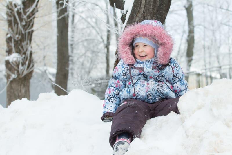 De winter openluchtportret van het lachen meisjezitting bovenop sneeuwheuvel stock fotografie