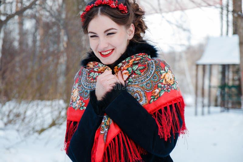 De winter portreit glimlachend meisje met mooi haar op haar hoofd in Russische volksstijl in rode sjaals royalty-vrije stock foto's