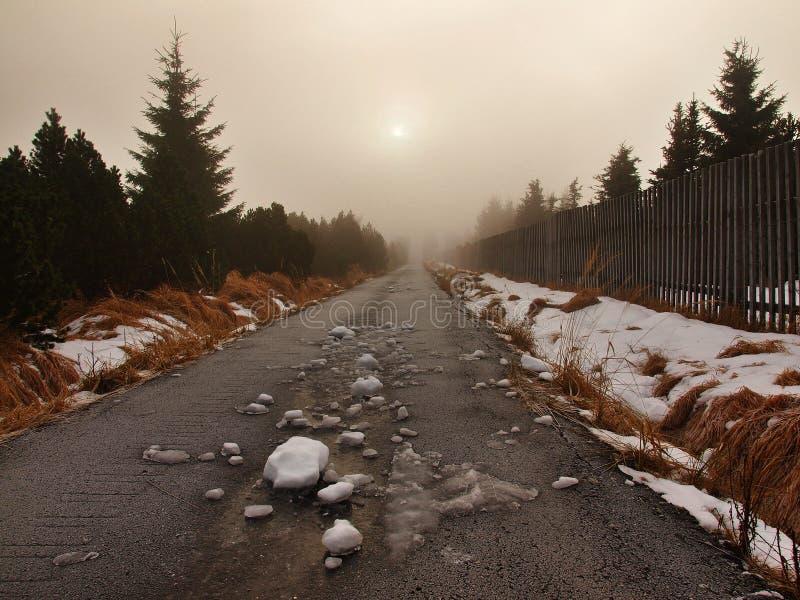 De winter stormachtig weer in bergen, donkere sneeuwwolken, koude sneeuw in de hemel. De weg door sneeuw en ijs wordt behandeld da stock foto's