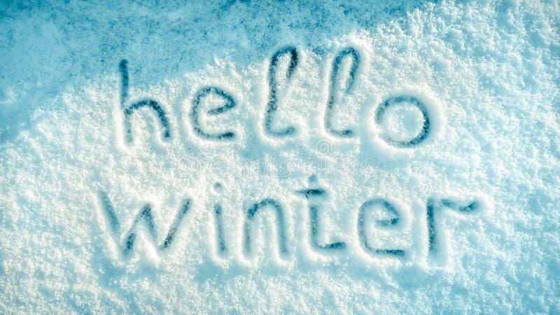 De winter van de handschrifttekst 'hello 'op de verse witte achtergrond van de sneeuwtextuur stock afbeelding