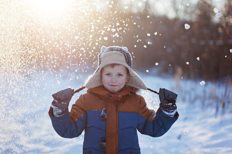 De winter weinig kind werpt het spelen in openlucht op sneeuw tijdens sneeuwval Actieve outoorsvrije tijd met kinderen in de wint royalty-vrije stock afbeeldingen