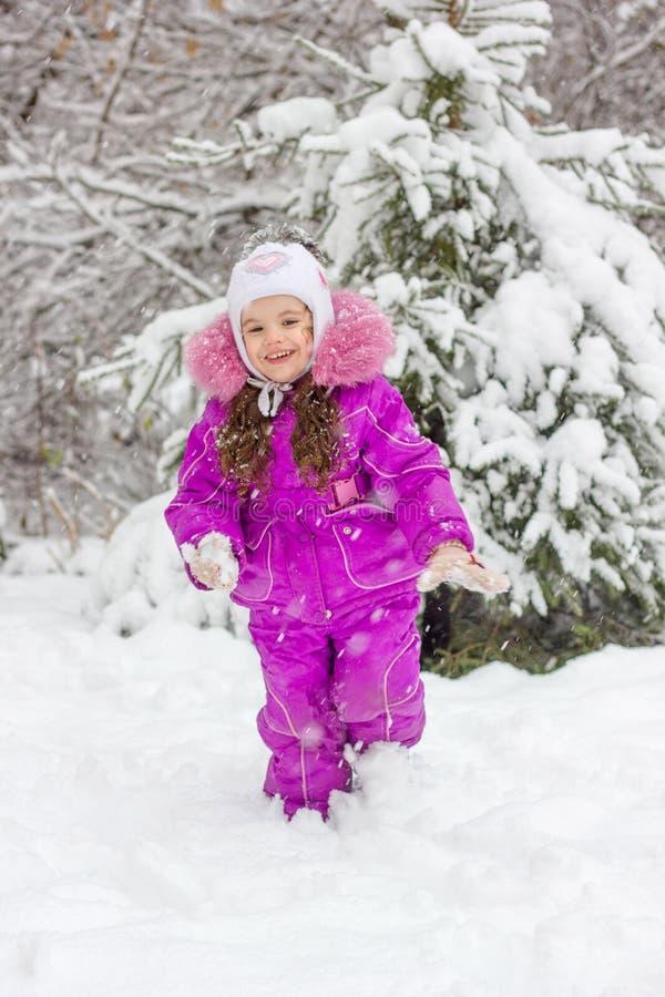 De winteractiviteit - meisje het spelen sneeuwballen stock afbeeldingen