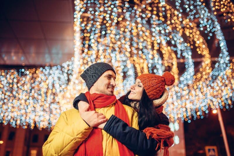 De winteravond, het glimlachen de omhelzingen van het liefdepaar op straat royalty-vrije stock afbeelding