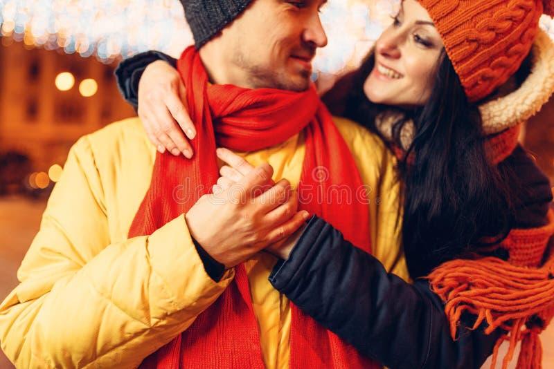De winteravond, het glimlachen de omhelzingen van het liefdepaar op straat stock fotografie