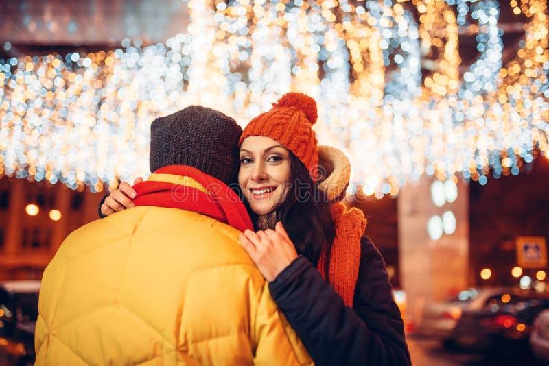 De winteravond, de omhelzingen van het liefdepaar op de straat stock fotografie
