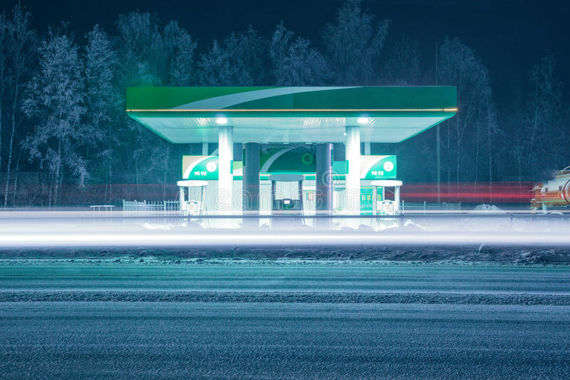 De winterbenzinestation bij nacht met lange lichte sporen van de koplampen van het overgaan van auto's stock afbeelding
