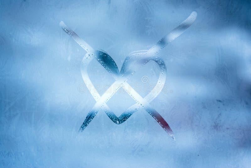 De winterconcept van de liefdeeenzaamheid Gekruist hart met de hand geschreven symbool op het glasvenster met bevroren patronen royalty-vrije stock foto