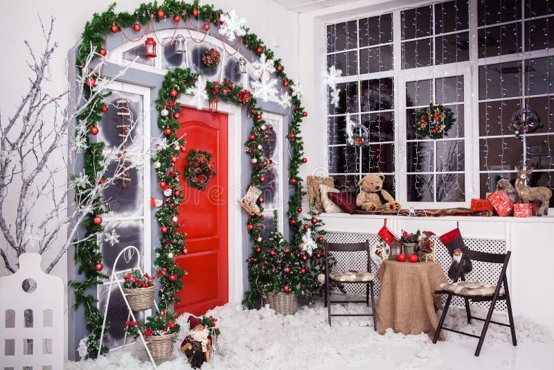De winterdecoratie Rode deur met Kerstmiskroon royalty-vrije stock foto's