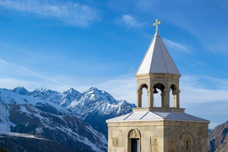 De winterlandschap in Kazbegi: de bergen en St Ilya Orthodox Church van de Kaukasus stock afbeelding