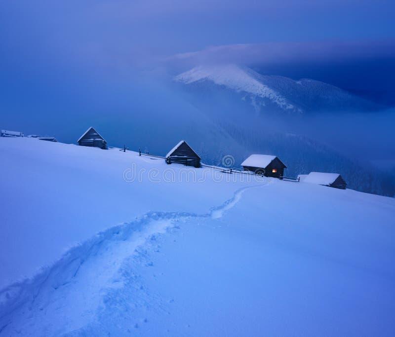 De winterlandschap met berghutten en een weg in de sneeuw royalty-vrije stock foto