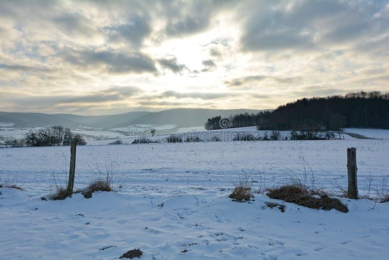 De winterlandschap met de zonsopgang met houten post royalty-vrije stock afbeeldingen