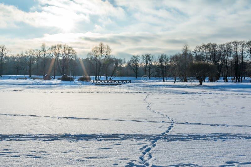 De winterlandschap met een bevroren meer, voetafdrukken in de sneeuw, royalty-vrije stock foto's