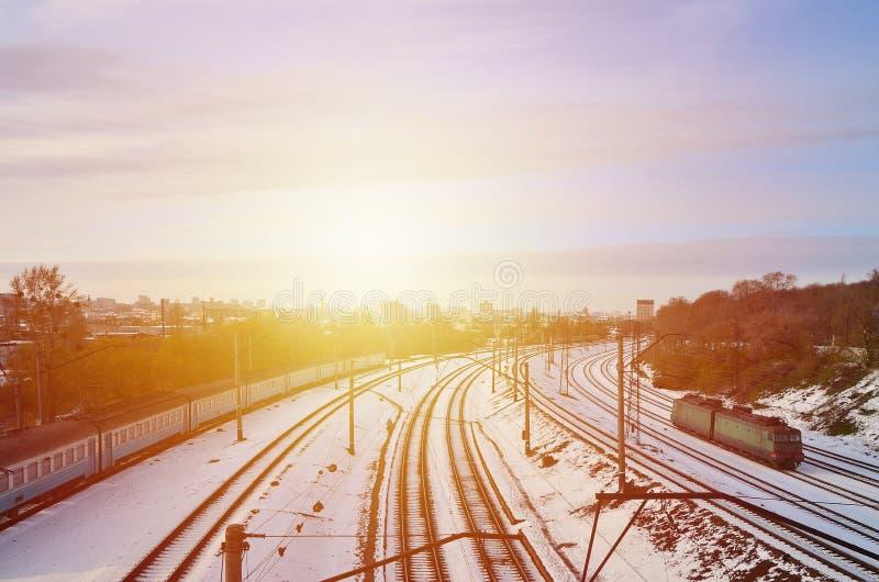 De winterlandschap met een spoorwegtrein op een spoorweg door een stadspanorama met veel huizen en gebouwen tegen een clou wordt  royalty-vrije stock foto's