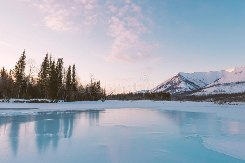 De winterlandschap op de bergen en het bevroren meer in Yakutia, Siberië, Rusland Lichtrose wolken in het ochtendlicht stock fotografie