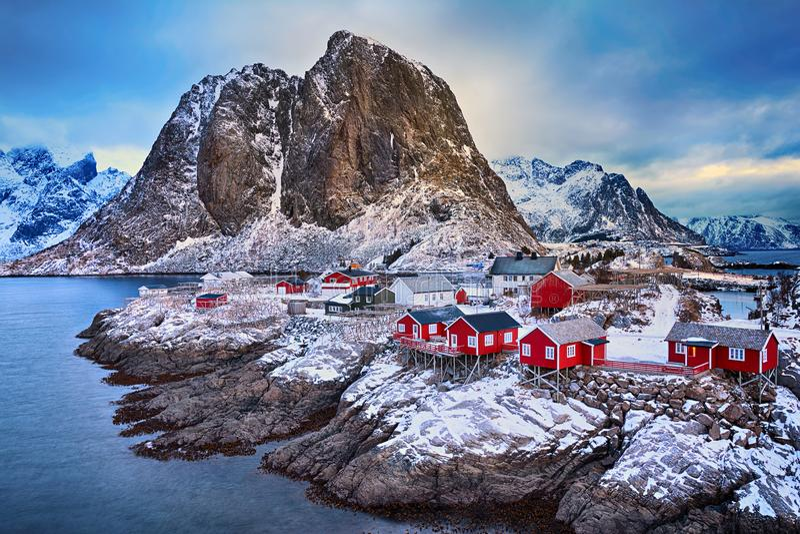 De winterlandschap van schilderachtig visserijdorp met rode rorbus in de bergen van Lofoten-eilanden stock fotografie