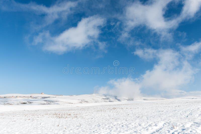 De winterlandschap, wolken op helling van een sneeuwberg stock fotografie