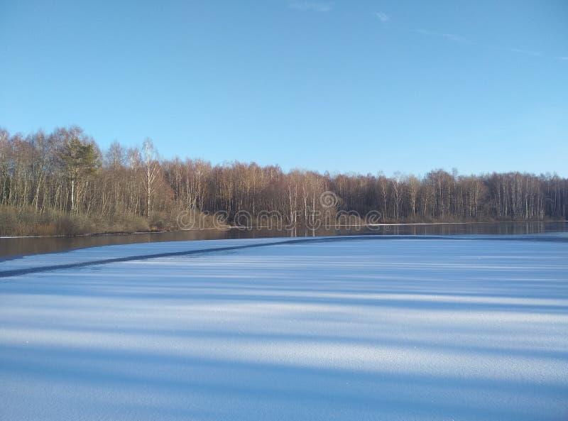 De wintermeer in de sneeuw Op de horizon bos Blauwe ijzige hemel Achtergrond behang royalty-vrije stock foto