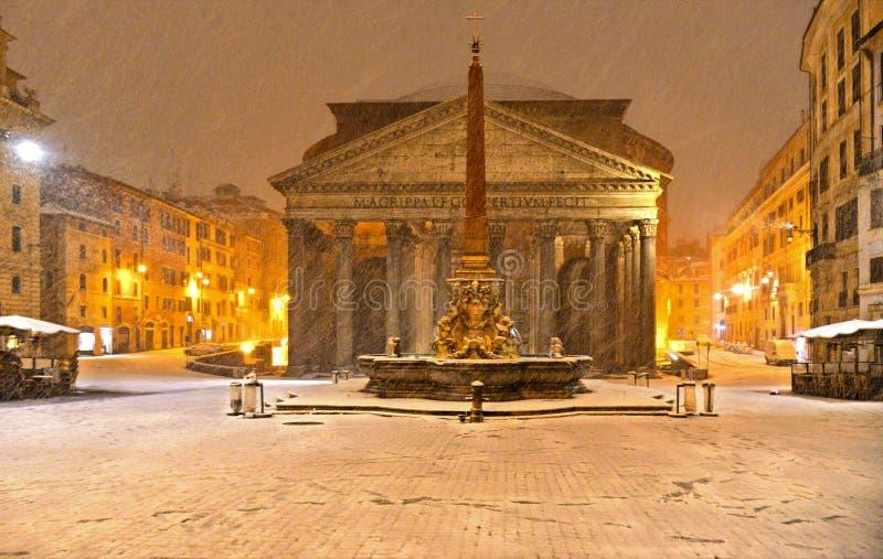 De winternacht in Rome met sneeuwblizzard en de kerk van de Pantheontempel in leeg vierkant met gouden licht, Italië stock afbeelding