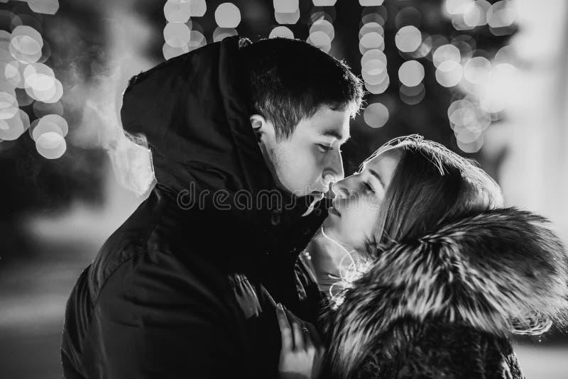 De winterpaar tegen kleurrijke gloeiende punten op zwarte royalty-vrije stock foto
