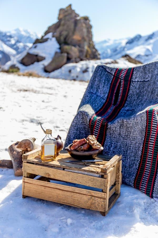 De de winterpicknick in Chileense Argentijnse sneeuwmountaines de Andes met heet vleesvoedsel en drankyerba koppelen stock fotografie