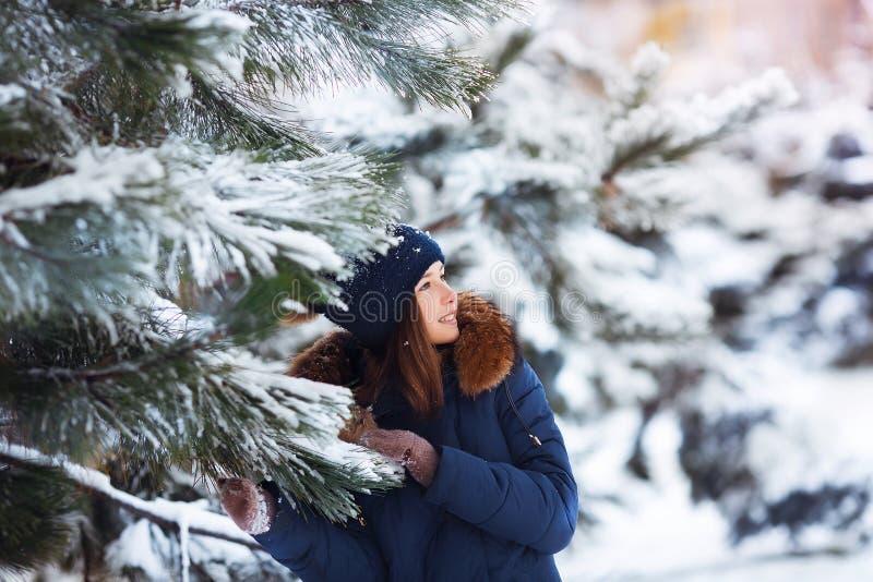 De winterportret van aanbiddelijk gelukkig kindmeisje die in warme kleren met sneeuw spelen stock foto