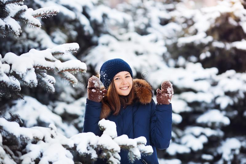 De winterportret van aanbiddelijk gelukkig kindmeisje die in warme kleren met sneeuw spelen stock foto's