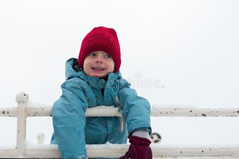 De winterportret van een kleine jongen in een rode hoed de baby glimlacht stock foto
