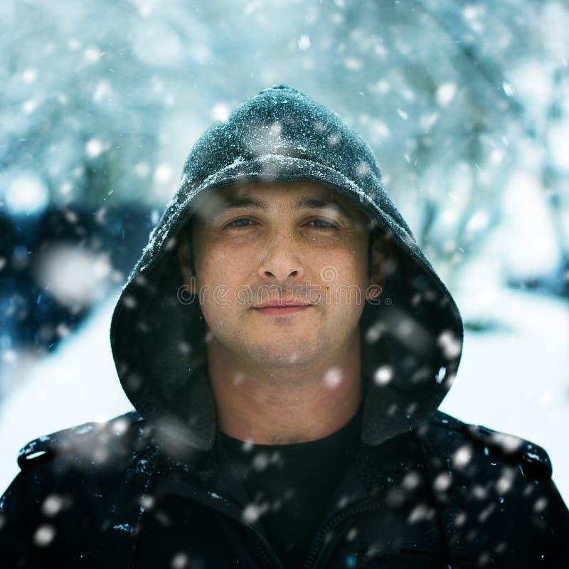 De winterportret van een mens die kap in sneeuw draagt stock afbeelding