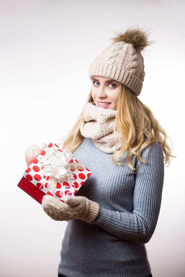De winterportret van een mooie jonge vrouw in warme gebreide kleren en met een gift op haar handen stock foto