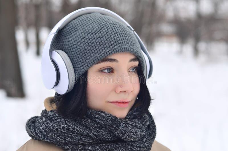 De winterportret van jong meisje met hoofdtelefoons royalty-vrije stock fotografie