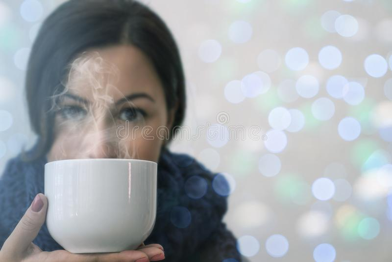 De winterportret van jonge donkerbruine vrouw met kop thee die gebreide haarband dragen stock foto's