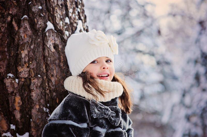 De winterportret van mooie het glimlachen kindmeisje status door de boom royalty-vrije stock afbeelding
