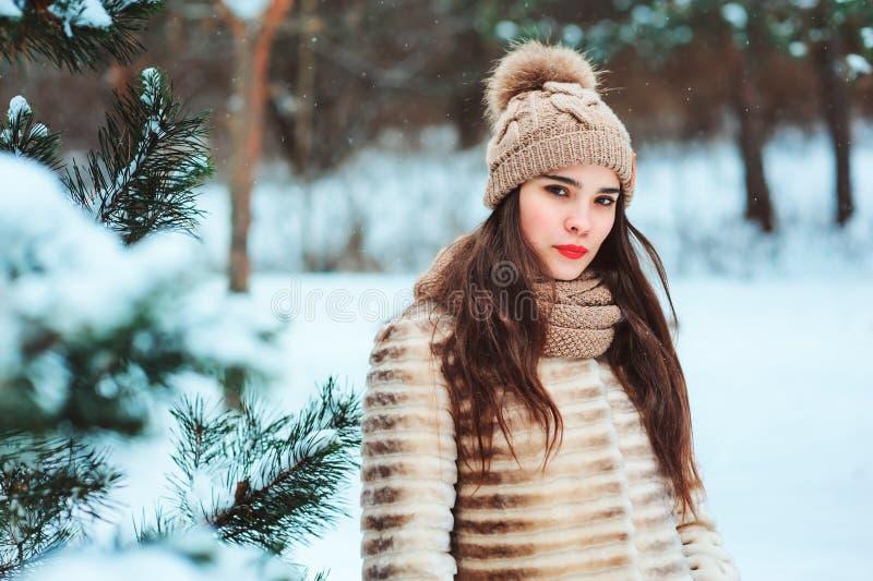 De winterportret van mooie jonge vrouw in bontjas en gebreide hoed royalty-vrije stock foto