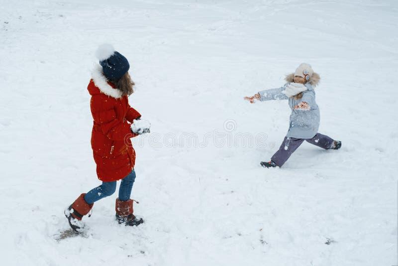 De winterportret van twee meisjes die pret, kinderen hebben die met s spelen stock afbeeldingen