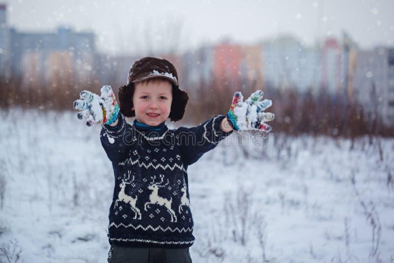 De winterportret van weinig jong geitjejongen die een gebreide sweater met deers dragen, in openlucht tijdens sneeuwval stock afbeeldingen