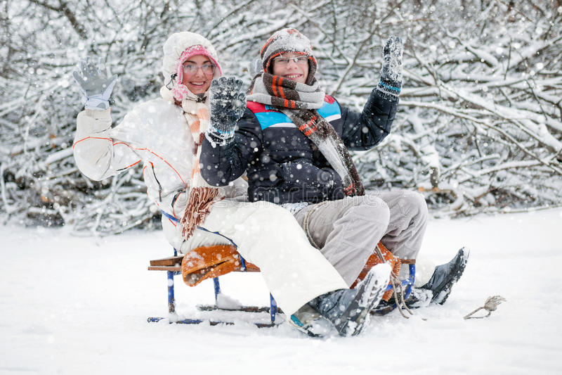 De winterpret, jongen en een meisje die in de wintertijd sledding stock foto