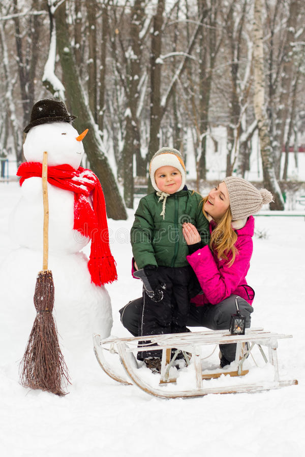 De winterpret met sneeuwman in hoed en rode sjaalmamma en zoon royalty-vrije stock foto's
