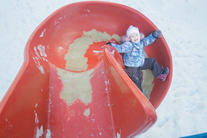 De winterpret van meisje op rode plastic speelplaatsdia stock foto