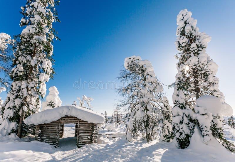 De wintersneeuw behandelde houten hut Bevroren blokhuis in Finland royalty-vrije stock afbeelding