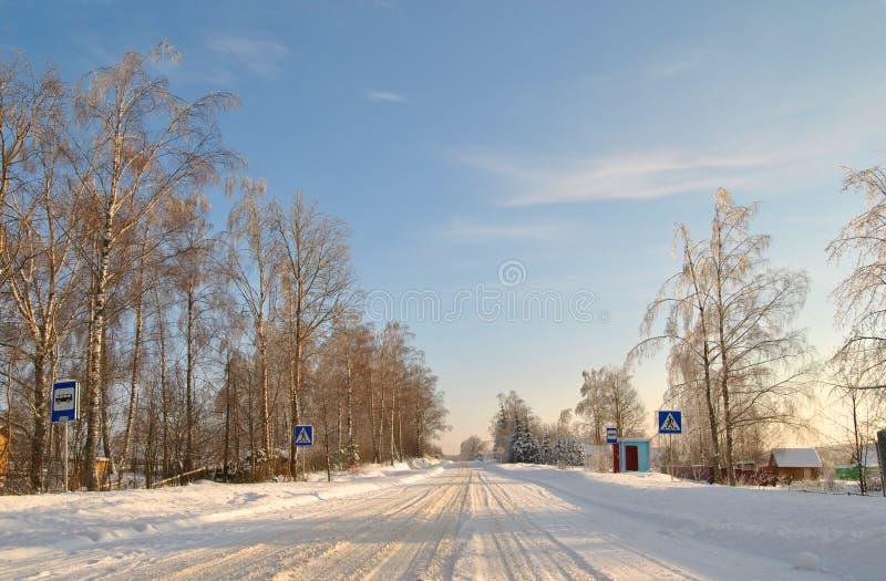 De wintersneeuw behandelde landweg op een zonnige dag stock afbeelding