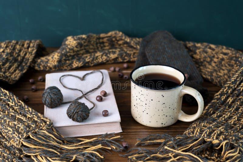 De winterstilleven met koffie, sjaal en boek op een houten lijst royalty-vrije stock foto