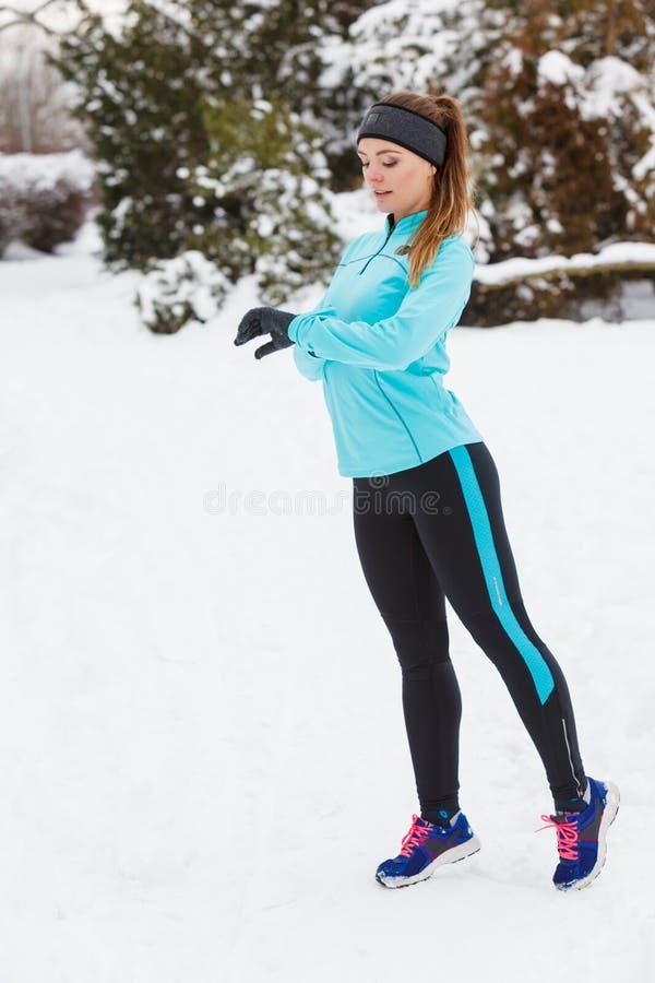 De wintertraining Meisje die sportkleding dragen, die horloge bekijken stock afbeeldingen