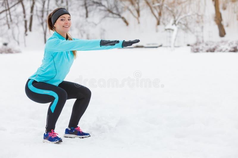 De wintertraining Meisje die sportkleding dragen die hurkzit doen stock afbeeldingen