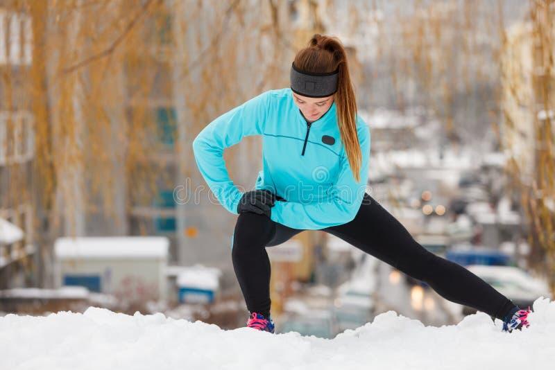 De wintertraining Meisje die sportkleding dragen, uitrekt oefeningen royalty-vrije stock foto's