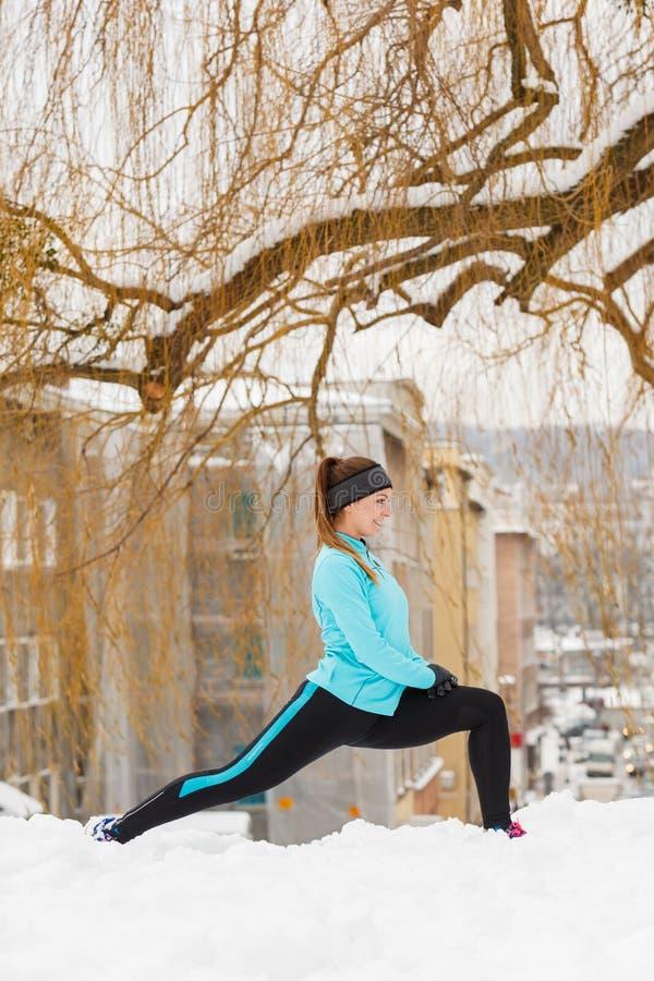 De wintertraining Meisje die sportkleding dragen, uitrekt oefeningen stock afbeeldingen