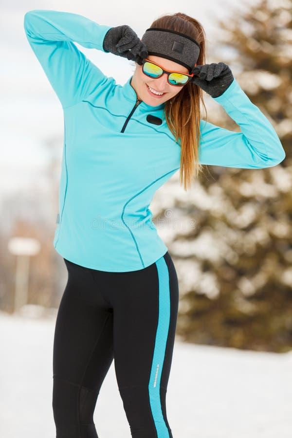 De wintertraining Meisje die sportkleding en zonnebril dragen stock foto's
