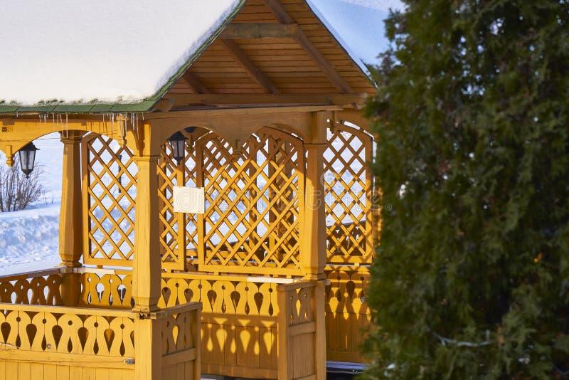De wintervakantie in aard Houten verandagazebo met decoratieve installatie in de stralen van de zon van de avondwinter stock afbeelding