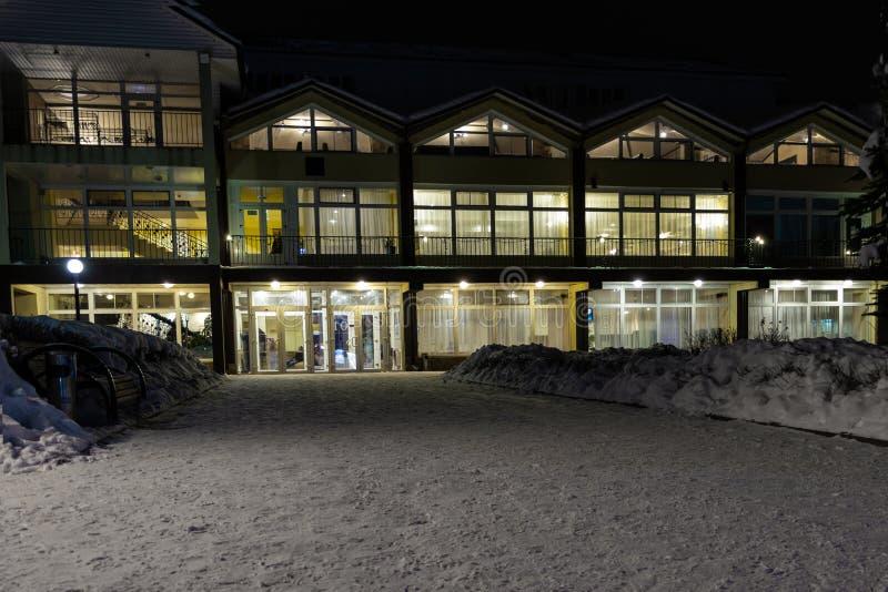 De wintervakantiewoning bij Kerstmis Een sneeuwweg, lichten in de vensters, een de wintersprookje Familievakantie voor royalty-vrije stock afbeeldingen