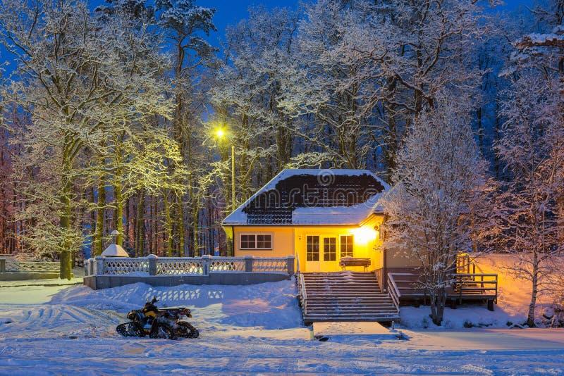 De winterverhaal - sneeuwscooter dichtbij comfortabel blokhuis en bevroren meer Sneeuw ijzige de winteravond royalty-vrije stock afbeelding